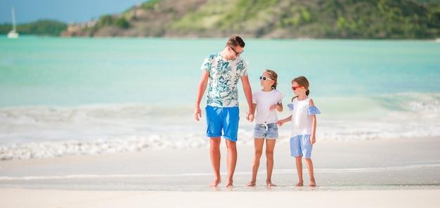 Junger vater und ihre entzückenden kleinen töchter am strand