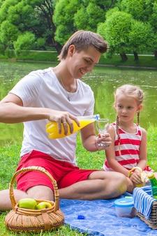 Junger vater und kleine tochter haben picknick im freien