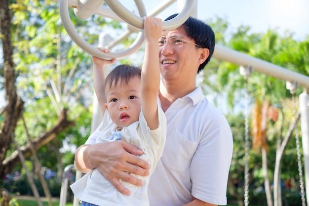 Junger vater und nettes kleines asiatisches kleinkind-babykind mit 2-jährigen, das das spaßtrainieren im freien hat und vati helfen, aufzuholen