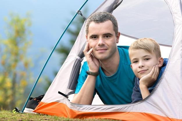 Junger vater und sein kindersohn wandern zusammen in der sommernatur. aktives familienreisekonzept.