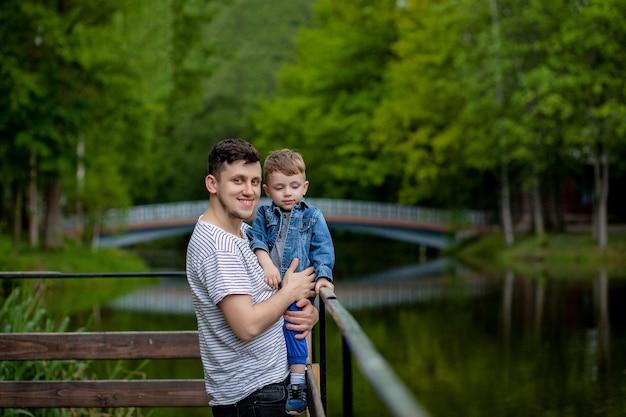 Junger vater und sein lächelnder sohn im park, umarmen und genießen zeit zusammen, vatertagsfeier.