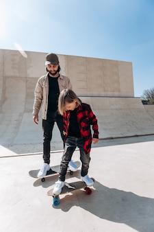 Junger vater und sein sohn fahren skateboards in einem skatepark mit rutschen draußen am sonnigen tag.