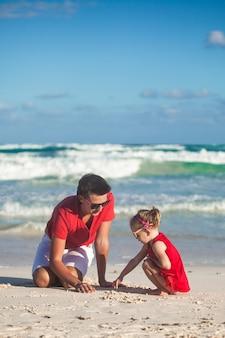 Junger vater und seine entzückende kleine tochter, die auf den sand am strand zeichnet
