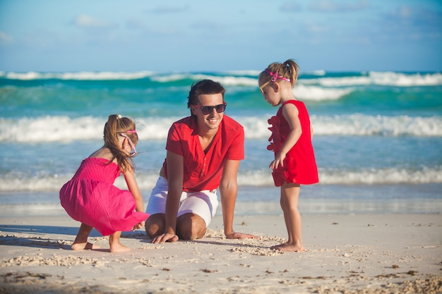 Junger vater und seine entzückenden kleinen töchter, die auf dem strand spielen