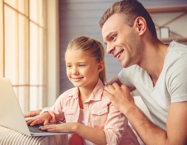 Junger vater und seine kleine tochter benutzen einen laptop.