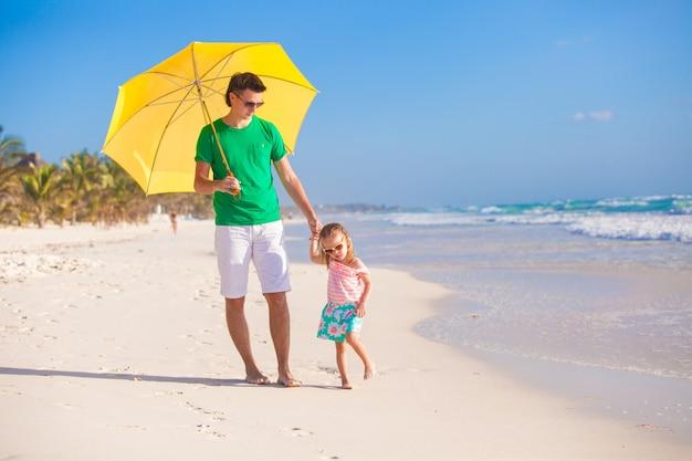 Junger vater und seine kleine tochter, die unter einen gelben regenschirm auf weißem sandstrand geht