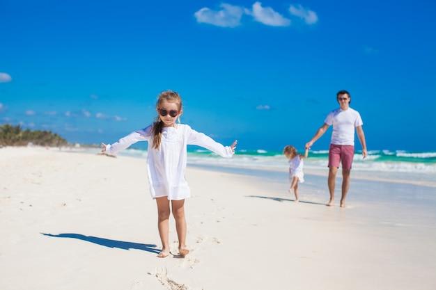Junger vater und seine kleinen entzückenden töchter, die spaß auf weißem strand haben