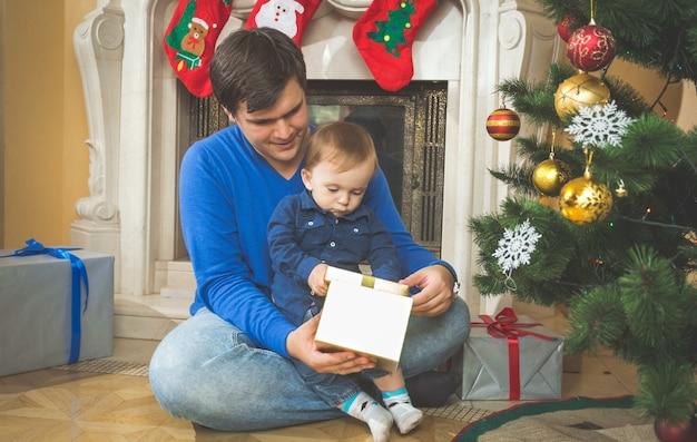 Junger vater und süßer babysohn öffnen weihnachtsgeschenke auf dem boden