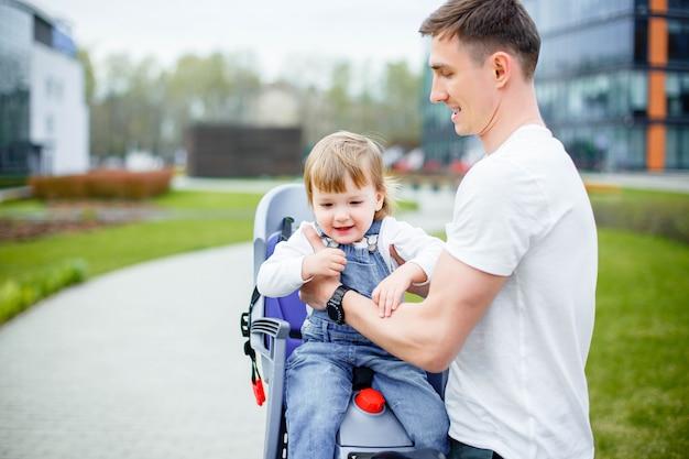 Junger vati, der eine kleine tochter in einem stuhl setzt, bevor fahrrad gefahren wird.