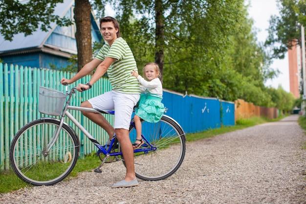 Junger vati rollt seine süße reizend tochter auf einem fahrrad in der landschaft
