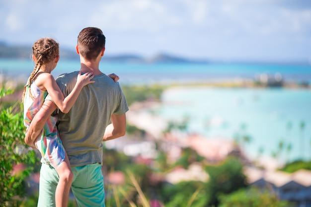 Junger vati und kind mit ansicht des tropischen weißen strandes in der exotischen insel im karibischen meer