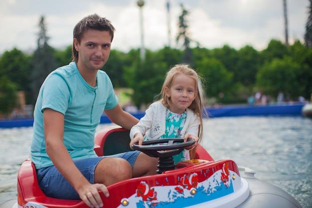 Junger vati und sein kleines mädchen, die auf ein luftboot in der anziehungskraft reitet