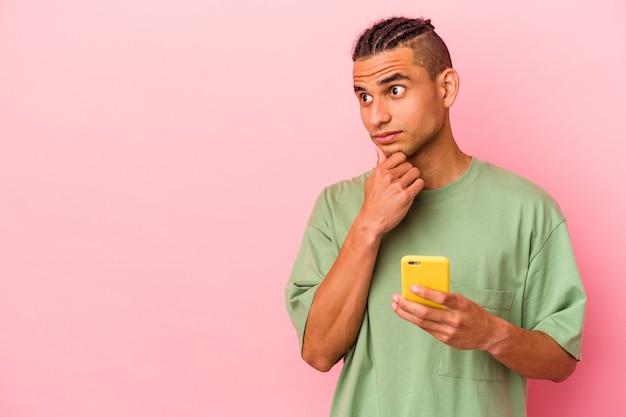 Junger venezolanischer mann, der ein mobiltelefon isoliert auf rosa wand hält und seitlich mit zweifelhaftem und skeptischem ausdruck schaut