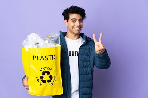 Junger venezolanischer mann, der eine tasche voller plastikflaschen hält, die lächeln und siegeszeichen zeigen