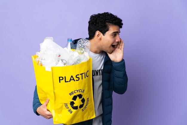 Junger venezolanischer mann, der eine tasche voller plastikflaschen hält, die mit weit geöffnetem mund zur seite schreien