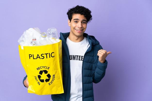Junger venezolanischer mann, der eine tasche voller plastikflaschen hält, die zur seite zeigen, um ein produkt zu präsentieren