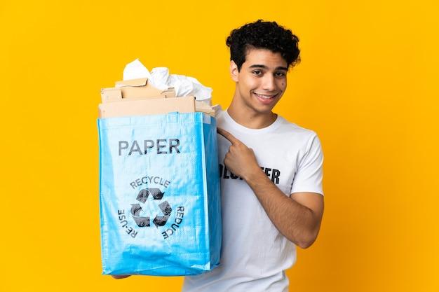 Junger venezolanischer mann, der einen recyclingbeutel voll papier hält, um zu zeigen, zur seite zu zeigen, um ein produkt zu präsentieren