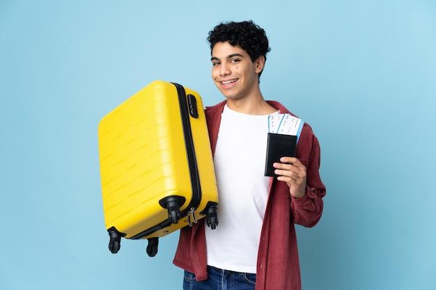 Junger venezolanischer mann lokalisiert auf blau im urlaub mit koffer und pass
