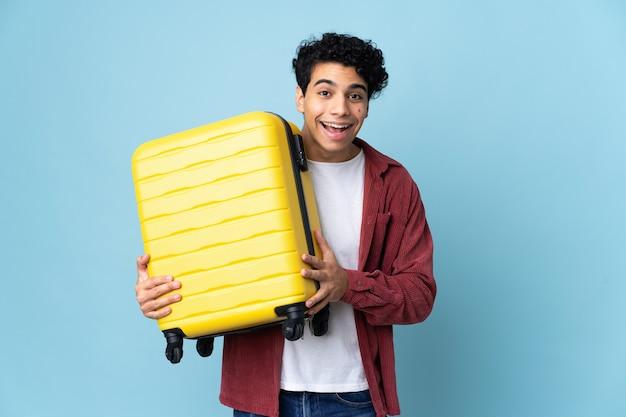 Junger venezolanischer mann lokalisiert auf blau im urlaub mit reisekoffer und überrascht