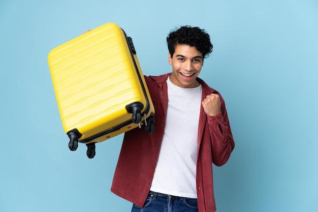 Junger venezolanischer mann lokalisiert auf blau im urlaub mit reisekoffer