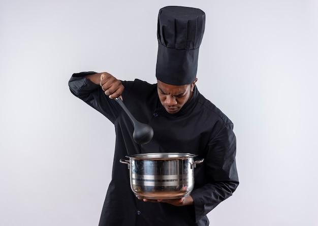 Junger verärgerter afroamerikanischer koch in der kochuniform hält topf und löffel lokalisiert auf weißem hintergrund mit kopienraum