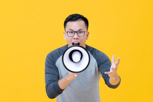 Junger verärgerter asiatischer mann, der in megaphon schreit