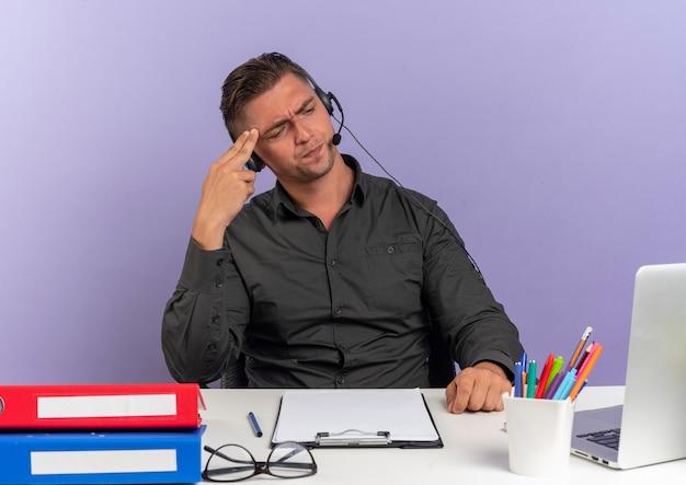 Junger verärgerter blonder büroangestelltermann auf kopfhörern sitzt am schreibtisch mit bürowerkzeugen, die laptop betrachten, setzt hand auf kopf lokalisiert auf violettem hintergrund mit kopienraum