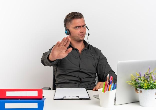 Junger verärgerter blonder büroangestelltermann auf kopfhörern sitzt am schreibtisch mit bürowerkzeugen unter verwendung von laptopgesten, die handzeichen lokalisiert auf weißem hintergrund mit kopienraum stoppen