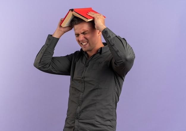 Junger verärgerter blonder gutaussehender mann hält buch über kopf isoliert auf violettem raum mit kopienraum