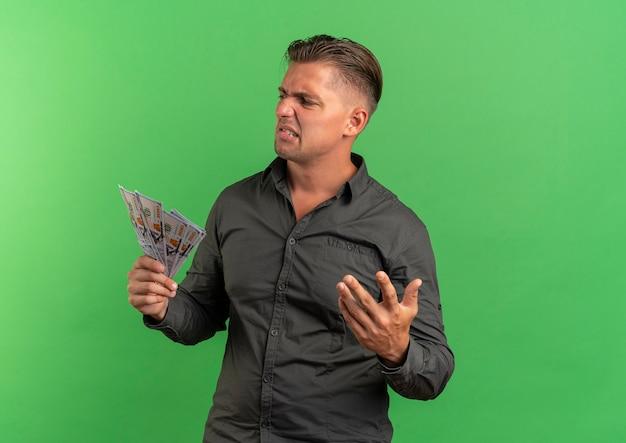 Junger verärgerter blonder gutaussehender mann hält geld mit erhabener hand, die seite lokalisiert auf grünfläche mit kopienraum betrachtet