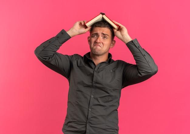 Junger verärgerter blonder hübscher mann hält buch über kopf lokalisiert auf rosa raum mit kopienraum