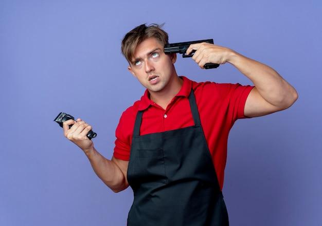 Junger verärgerter blonder männlicher friseur in der uniform hält pistole zum tempel, der nach oben hält und haarschneidemaschine isoliert auf violettem raum mit kopienraum hält