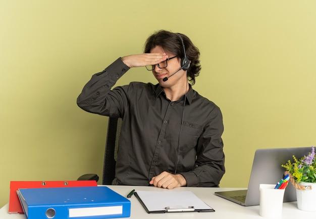 Junger verärgerter büroangestelltermann auf kopfhörern in optischen gläsern sitzt am schreibtisch mit bürowerkzeugen unter verwendung des laptops hält kopf lokalisiert auf grünem hintergrund mit kopienraum