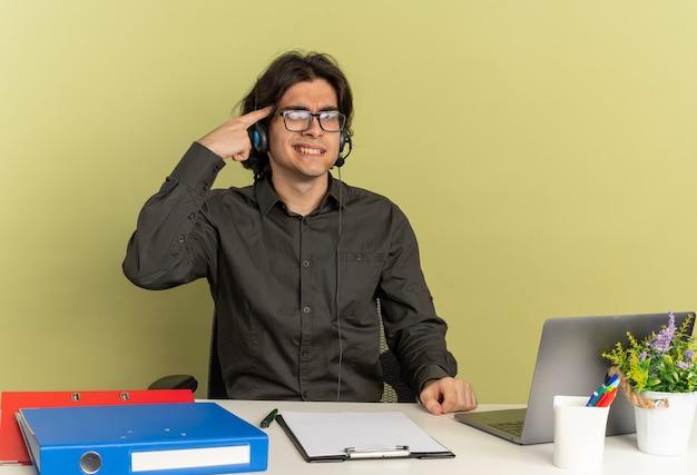 Junger verärgerter büroangestelltermann auf kopfhörern in optischen gläsern sitzt am schreibtisch mit bürowerkzeugen unter verwendung des laptops setzt finger auf kopf, der kamera lokalisiert auf grünem hintergrund mit kopienraum betrachtet