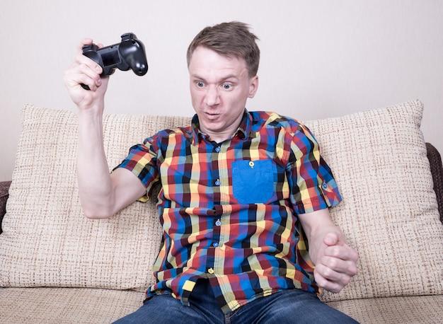 Junger verärgerter mann, der videospiele spielt