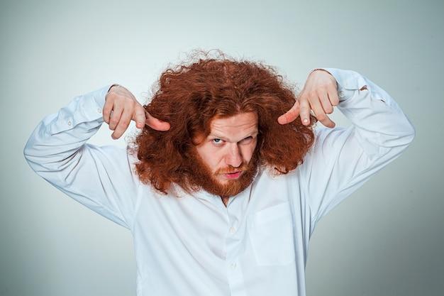 Junger verärgerter mann mit langen roten haaren