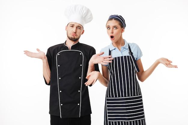 Junger verärgerter mannkoch in der schwarzen uniform und im weißen hut und in der frau kochen in gestreifter schürze und in der mütze erstaunt