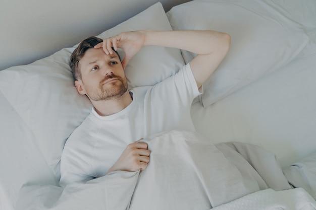 Junger verärgerter und müder bärtiger mann, der mit offenen augen auf dem bett liegt und nicht schlafen kann, mann mit schlaflosigkeitsproblemen oder schlafstörungen. konzept der schlafenszeit und der ruhephasen