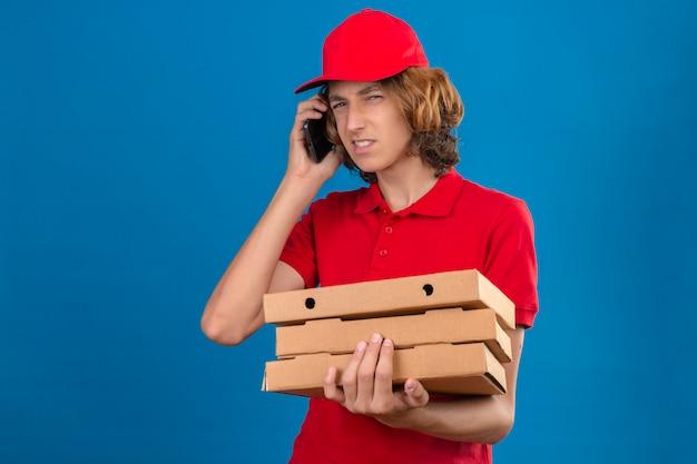Junger verdächtiger lieferbote in der roten uniform, die auf handy spricht, während pizzaschachteln über lokalisiertem blauem hintergrund halten