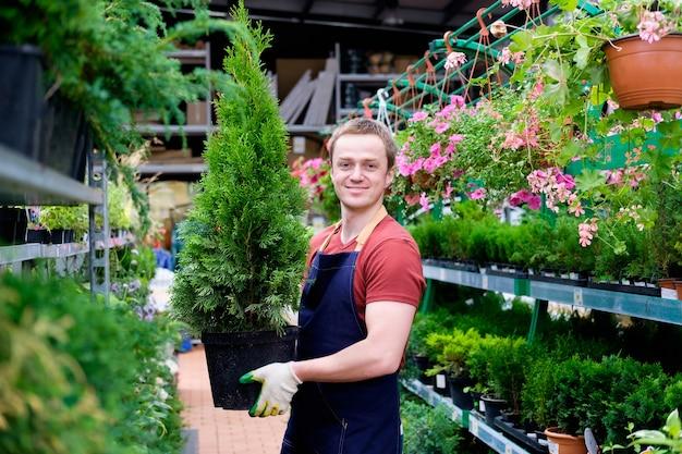 Junger verkäufer im pflanzenmarkt