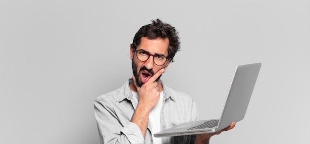 Junger verrückter bärtiger mann. denkender oder zweifelnder ausdruck. laptop-konzept