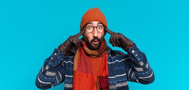 Junger verrückter bärtiger mann. denkender oder zweifelnder ausdruck und tragen winterkleidung