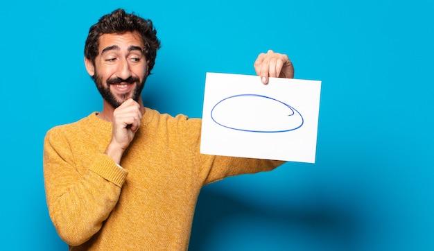 Junger verrückter bärtiger mann, der ein blatt papier mit einem kopienraum zeigt