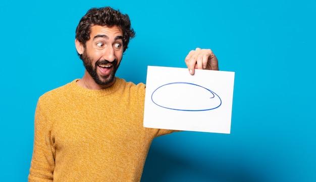 Junger verrückter bärtiger mann, der ein blatt papier mit einem kopierraum zeigt showing Premium Fotos