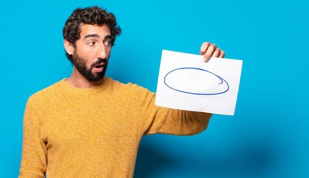 Junger verrückter bärtiger mann, der ein blatt papier mit einem kopierraum zeigt