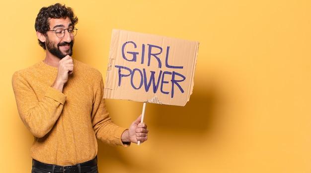 Junger verrückter bärtiger mann, der ein mädchen-power-banner hält