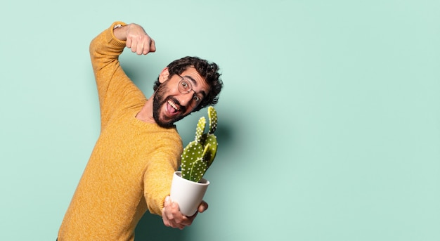 Junger verrückter bärtiger mann, der eine kaktus-zimmerpflanze hält