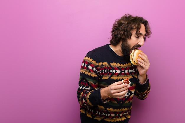 Junger verrückter bärtiger mann, der einen burger isst