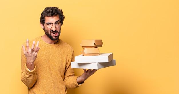 Junger verrückter bärtiger mann, der fast food mit einem kopienraum wegnimmt