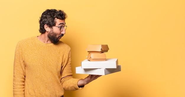 Junger verrückter bärtiger mann, der fast food mit einem kopierraum wegnimmt